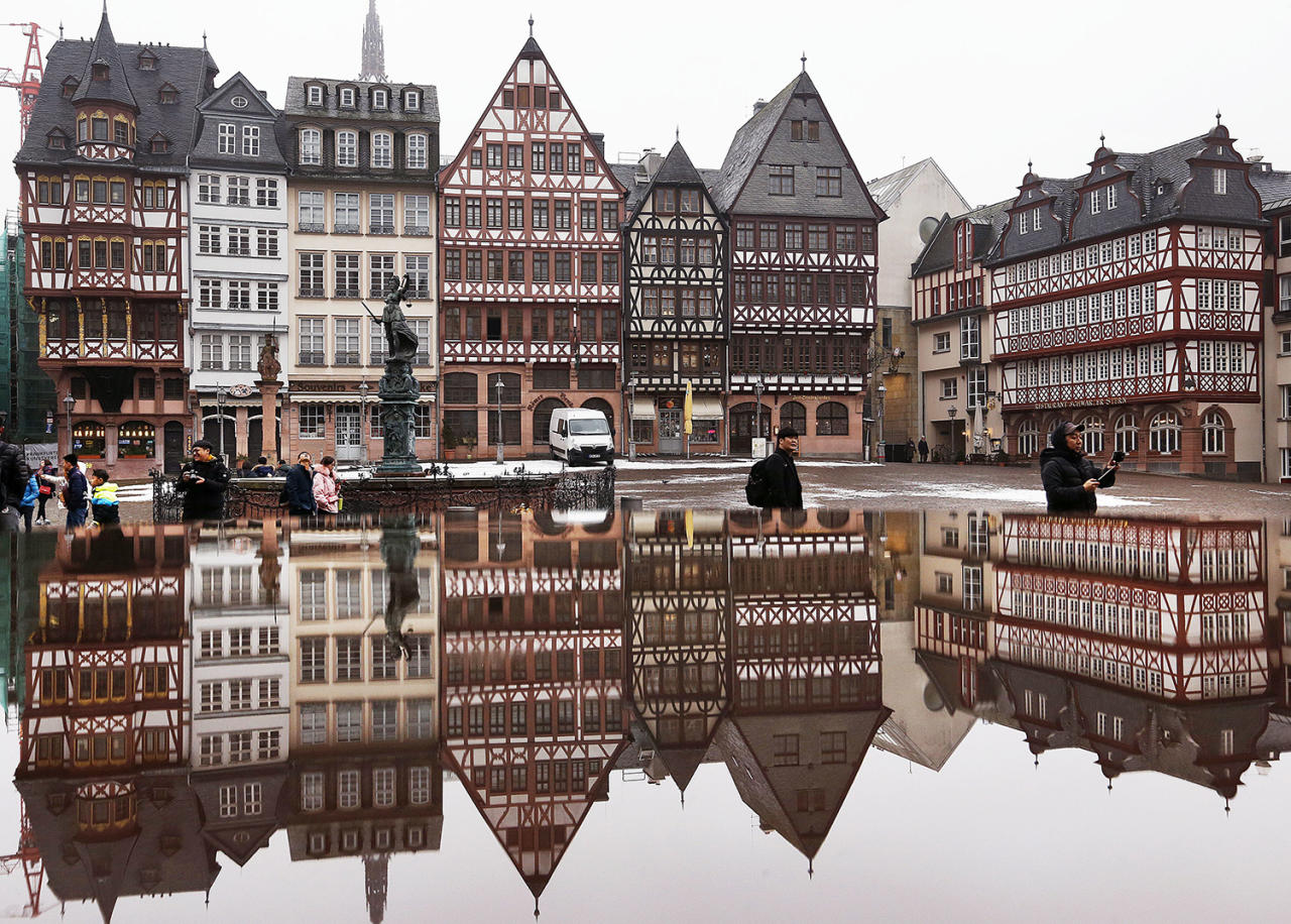 <p>Timber-framed houses in the Roemerberg square are reflected in water in Frankfurt, Germany, Jan. 11, 2017. (Photo: Michael Probst/AP) </p>
