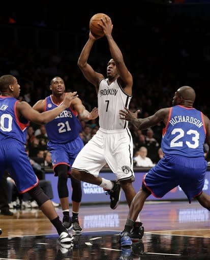 Brooklyn Nets' Joe Johnson, center, takes the ball to the basket through Philadelphia 76ers defenders during the first half of an NBA basketball game at the Barclays Center Sunday, Dec. 23, 2012 in New York. (AP Photo/Seth Wenig)