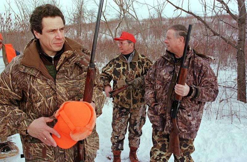 FILE - In this Sunday, Jan. 23, 2000 file photo, Housing and Urban Development Secretary Andrew Cuomo, left, gets ready for a pheasant hunt in Savannah, N.Y., as New York assemblymen Dick Smith, center, of Buffalo, N.Y., and Michael Bragman, right, of Cicero, N.Y., stand with him. Lobbying for gun control in the United States sometimes means showing how much you like firearms. New York Gov. Andrew Cuomo, whose state recently passed some of the strictest gun control measures in the country, often reminds people he is a hunter. (AP Photo/Michael Okoniewski, File)