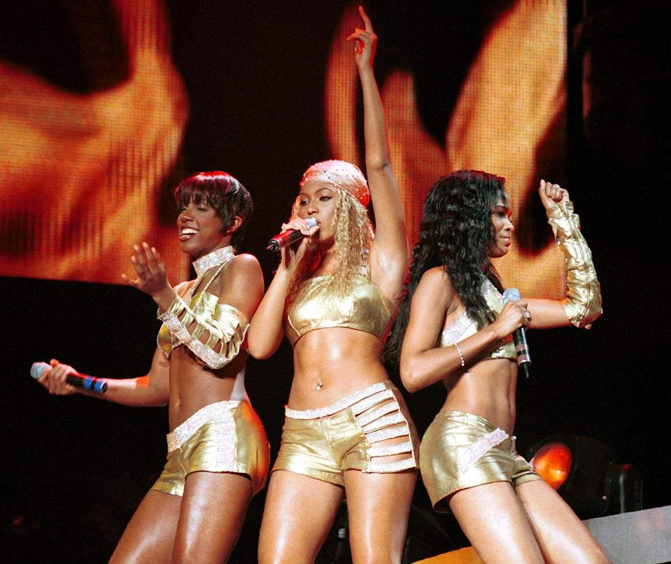<p>Performing on MTV's TRL in 2001 wearing matching gold booty shorts and crop tops. </p>
