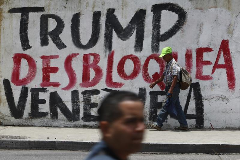 """People walk past a mural with a message that reads in Spanish: """"Trump unblock Venezuela"""", in Caracas, Venezuela, Tuesday, Aug. 6, 2019. Donald Trump signed an executive order Monday freezing Venezuelan government assets in significant escalation of tensions with Nicolas Maduro. While the order falls short of an outright trade embargo it represents the most sweeping U.S. action to remove Maduro since the Trump administration recognized Juan Guaido as Venezuela's rightful leader in January. (AP Photo/Leonardo Fernandez)"""