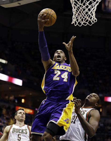 Los Angeles Lakers' Kobe Bryant (24) shoots against Milwaukee Bucks' J.J. Redick, left, and Samuel Dalembert during the first half of an NBA basketball game, Thursday, March 28, 2013, in Milwaukee. (AP Photo/Jeffrey Phelps)