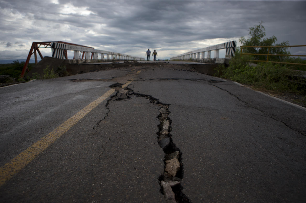 <p>Men walk across the bridge that connects Juchitan to Union Hidalgo in Oaxaca state, Mexico, Sunday, Sept. 10, 2017. While the bridge survived Thursday's magnitude 8.1 earthquake, the road leading up to each side fissured and the supporting walls buckled. Wary of using the bridge, taxis are now waiting on either side to ferry passengers, who cross the bridge on foot. (AP Photo/Rebecca Blackwell) </p>
