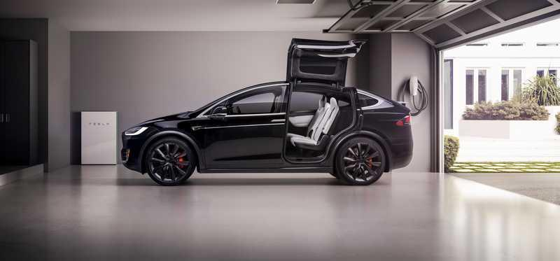 A Model X in a garage with its falcon wing doors open.