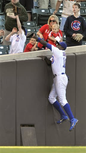 Chicago Cubs left fielder Alfonso Soriano attempts to catch a foul ball hit by Cincinnati Reds' Derrick Robinson during the 14th inning of a baseball game in Chicago, Thursday, June 13, 2013. Chicago won 6-5 in 14 innings. (AP Photo/Paul Beaty)