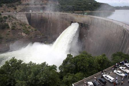 People watch as the spillway gates are opened at Kariba North Bank dam on Lake Kariba