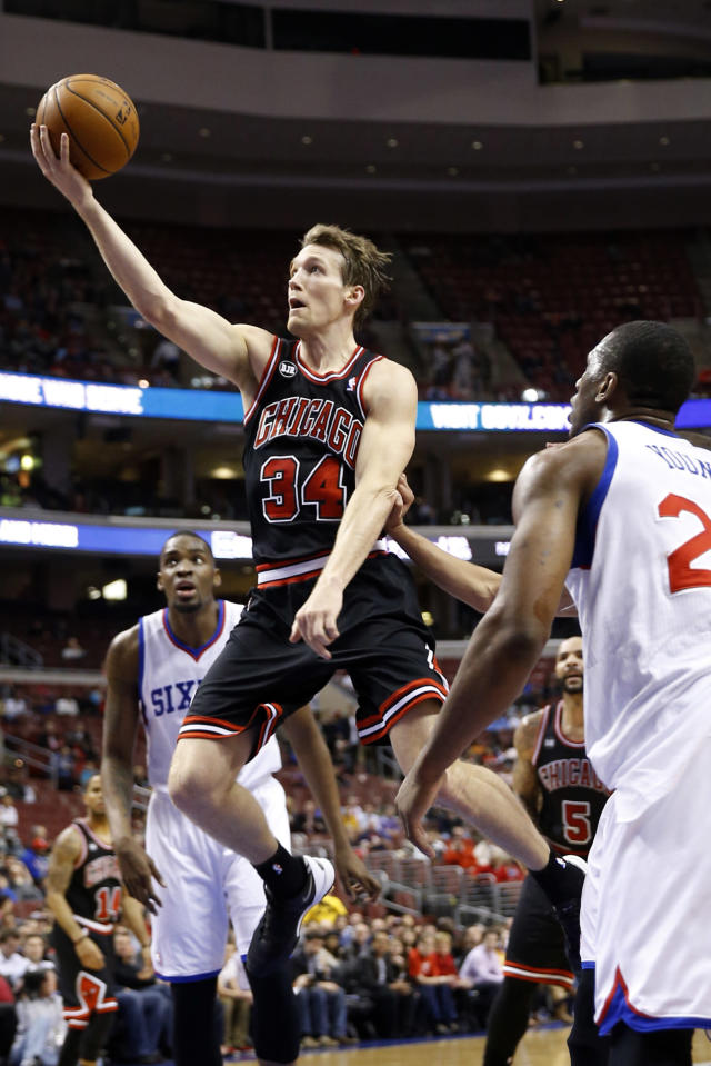 Chicago Bulls' Mike Dunleavy, center, goes up for a shot between Philadelphia 76ers' Jarvis Varnado, left, and Thaddeus Young during the first half of an NBA basketball game, Wednesday, March 19, 2014, in Philadelphia. (AP Photo/Matt Slocum)