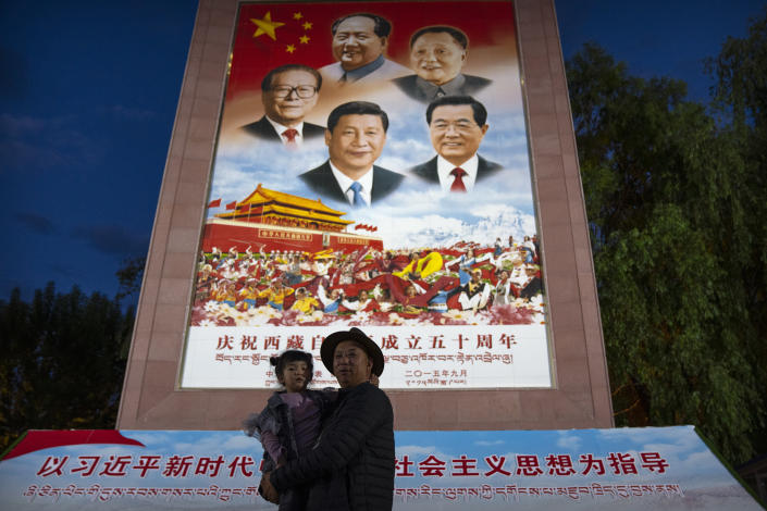 A man holds a girl as they pose for a photo in front of a large mural depicting Chinese President Xi Jinping, bottom center, and other Chinese leaders at a public square at the base of the Potala Palace in Lhasa in western China's Tibet Autonomous Region on June 1, 2021. Chinese leader Xi Jinping has made a rare visit to Tibet as authorities tighten controls over the Himalayan region's traditional Buddhist culture, accompanied by an accelerated drive for economic development and modernized infrastructure. (AP Photo/Mark Schiefelbein)