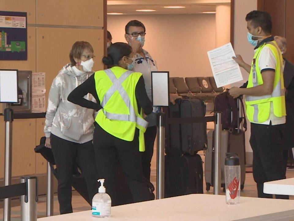 Airport staff inform passengers about new policies. (Pat Callaghan/CBC - image credit)