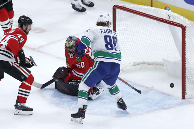 Vancouver Canucks' Adam Gaudette, right, is unable to get his stick on a bouncing puck as Chicago Blackhawks goaltender Corey Crawford (50) defends during the first period of an NHL hockey game Thursday, Nov. 7, 2019, in Chicago. (AP Photo/Charles Rex Arbogast)