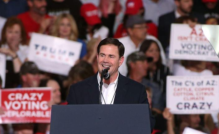 Arizona Governor Doug Ducey wears a black suit jacket and speaks into a microphone on a stage.