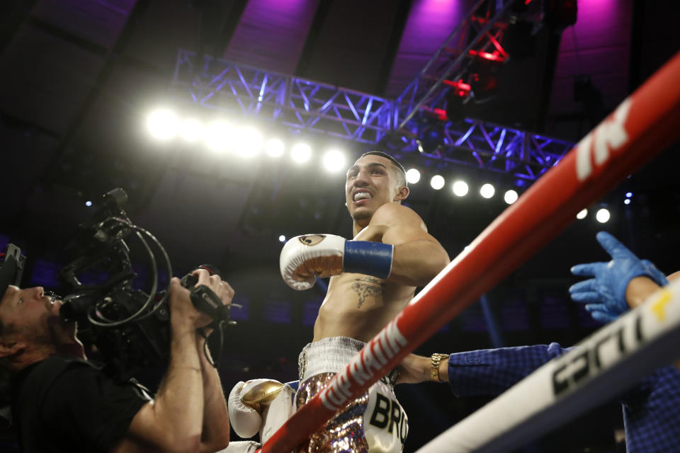 Teofimo Lopez, center, reacts after defeating Ghana's Richard Commey by TKO during the second round of an IBF lightweight boxing match, Saturday, Dec. 14, 2019, in New York. (AP Photo/Michael Owens)