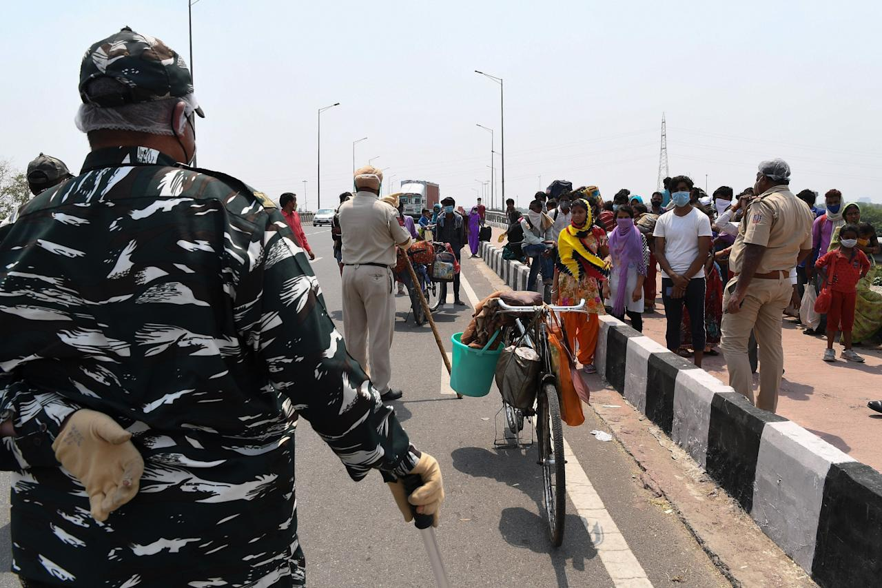 Security personnel stop migrant workers with their families walking back to their native places in Uttar Pradesh and Bihar state as the government eased a nationwide lockdown as a preventive mearure against the COVID-19 coronavirus, in New Delhi on May 14, 2020. (Photo by Prakash SINGH / AFP) (Photo by PRAKASH SINGH/AFP via Getty Images)