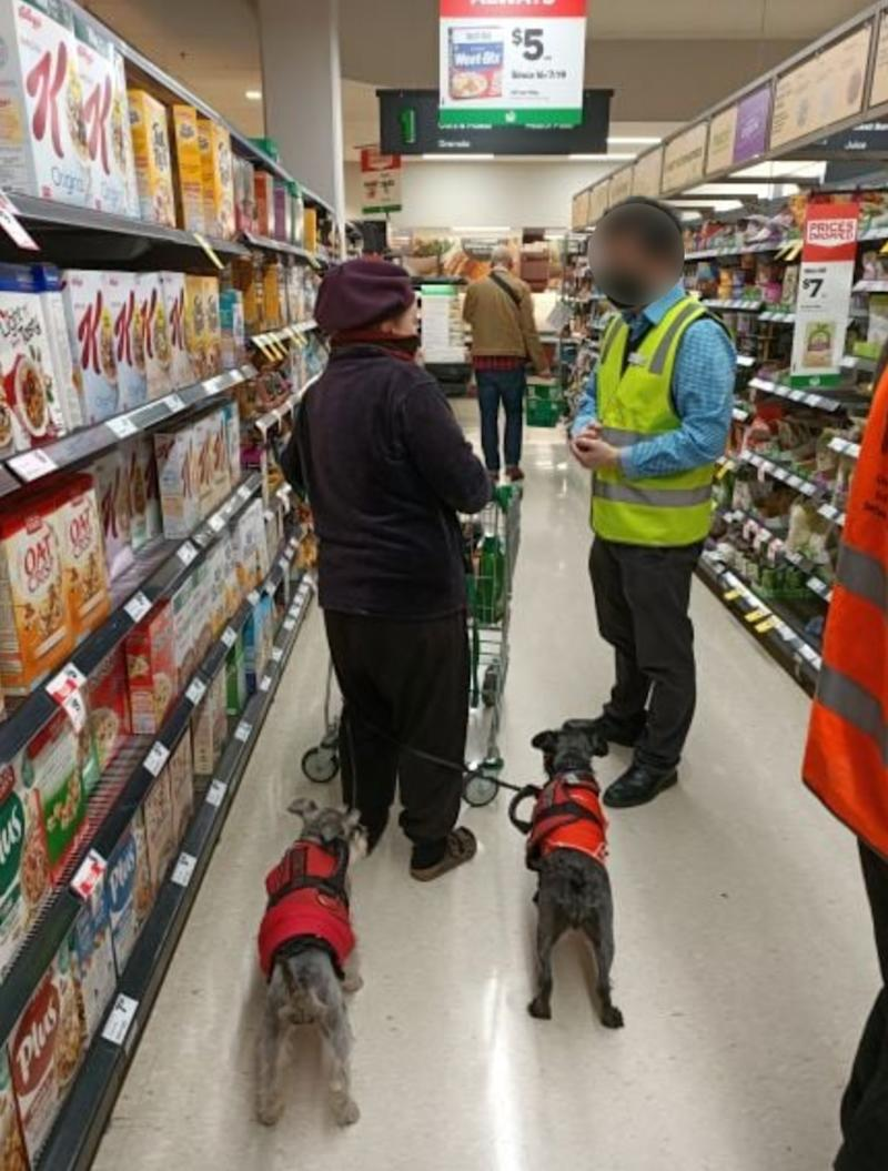 A Melbourne woman is pictured being spoken to by a Woolworths store manager on Saturday.