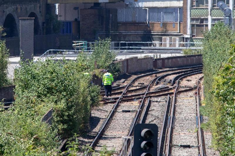 A police officer searches the tracks where three people were hit and killed by a train near Loughborough Junction