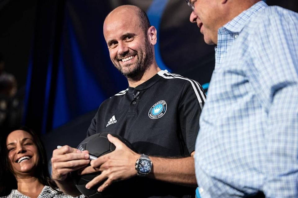 Charlotte FC's new Head Coach Miguel Ángel Ramírez smiles as he signs a ball at a press conference in Charlotte Thursday. The team's owner, David Tepper, is at right.