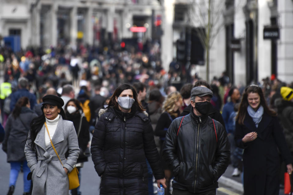 Shoppers walk wearing face masks and carrying shopping bags in Regent Street, after coronavirus restrictions were eased following the end of the second national lockdown in England, in London, Saturday, Dec. 5, 2020. (AP Photo/Alberto Pezzali)