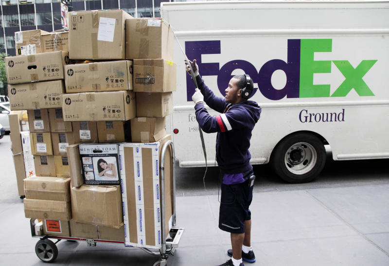 In this Friday, May 11, 2012, file photo, a FedEx worker sorts boxes for delivery as they are unloaded from a FedEx truck in New York. FedEx Corp. said Tuesday, June 19, 2012, that slow global growth will crimp its earnings results over the next 12 months, but it's vowing to make significant cost cuts to make up for any shortfall.(AP Photo/Mark Lennihan)