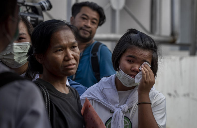 Relatives of mass shooting fatalities wait outside a morgue at Korat, Nakhon Ratchasima, Thailand, Sunday, Feb. 9, 2020. Thai officials say a soldier who went on a shooting rampage and killed numerous people and injured dozens of others has been shot dead inside the mall in northeastern Thailand. (AP Photo/Gemunu Amarasinghe)