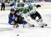 St. Louis Blues' Vince Dunn (29) and Dallas Stars' Justin Dowling (37) move to control the puck as Andrew Cogliano, rear, looks on during the second overtime period in Game 7 of an NHL second-round hockey playoff series, Tuesday, May 7, 2019, in St. Louis. (AP Photo/Jeff Roberson)