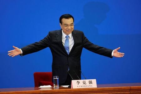 China's Premier Li Keqiang gestures as he arrives for a news conference after the closing ceremony of China's National People's Congress (NPC) at the Great Hall of the People in Beijing
