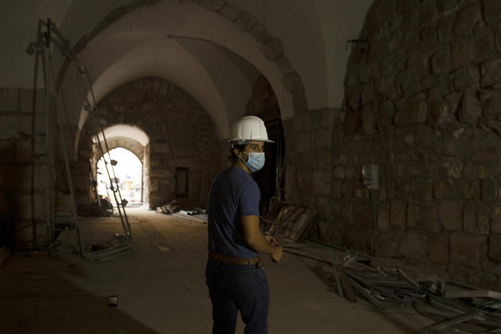 A staff member at the Tower of David Museum gives a tour to journalists in the Old City of Jerusalem, Wednesday, Oct. 28, 2020. The ancient citadel is devoid of tourists due to the pandemic and undergoing a massive restoration and conservation project. (AP Photo/Maya Alleruzzo)