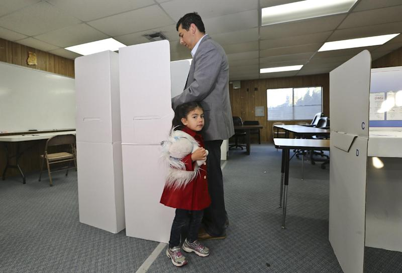 San Diego mayoral candidate David Alvarez cast his ballot as a his daughter, Izel, holds onto his leg at a polling location in the Logan Heights neighborhood where Alvarez grew up and still lives Tuesday, Feb. 11, 2014 in San Diego. (AP Photo/Lenny Ignelzi)