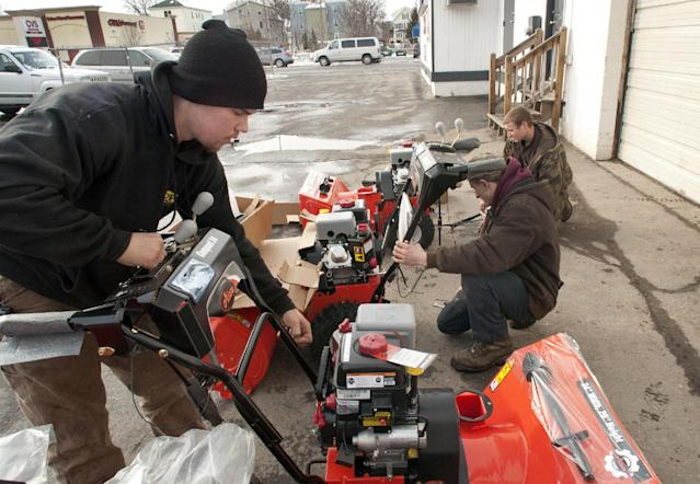 High school seniors and mechanics-in-training, from left, Tom Provost of Paxton, Mass., Matthew Hubert of Rutland, Mass., and Josh Ludden of Rutland, Mass set up and service six new snow blowers at Caola Equipment in Worcester, Mass. on Tuesday afternoon, Feb. 4, 2014. Up to a foot of snow if forecast for Central Massachusetts tomorrow. (AP Photo/Worcester Telegram & Gazette, Betty Jenewin)