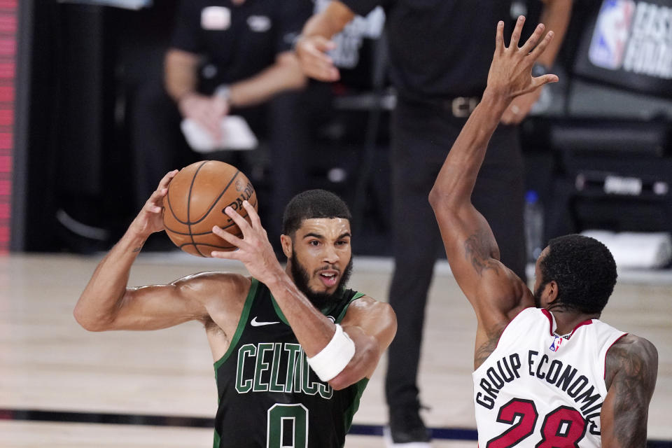 Boston Celtics' Jayson Tatum (0) is defended by Miami Heat's Andre Iguodala (28) during the second half of an NBA conference final playoff basketball game Friday, Sept. 25, 2020, in Lake Buena Vista, Fla. (AP Photo/Mark J. Terrill)