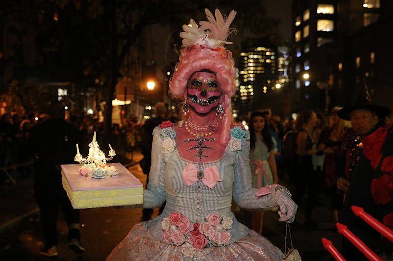 A ghoulish looking woman holding a cake marches in the Halloween Parade in New York City. (Photo: Gordon Donovan/Yahoo News)