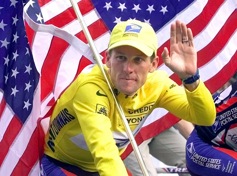 FILE - This July 23, 2000 file photo shows Tour de France winner Lance Armstrong riding down the Champs Elysees with an American flag after the 21st and final stage of the cycling race in Paris, France, Armstrong was stripped of his seven Tour de France titles and banned for life by cycling's governing body Monday, Oct. 22, 2012, following a report from the U.S. Anti-Doping Agency that accused him of leading a massive doping program on his teams. UCI President Pat McQuaid announced that the federation accepted the USADA's report on Armstrong and would not appeal to the Court of Arbitration for Sport. (AP Photo/Laurent Rebours, File)