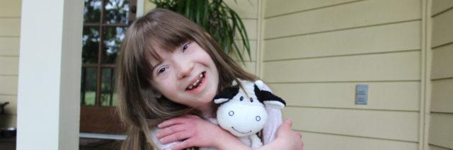 Child with Down syndrome hugging a stuffed cow and smiling at camera