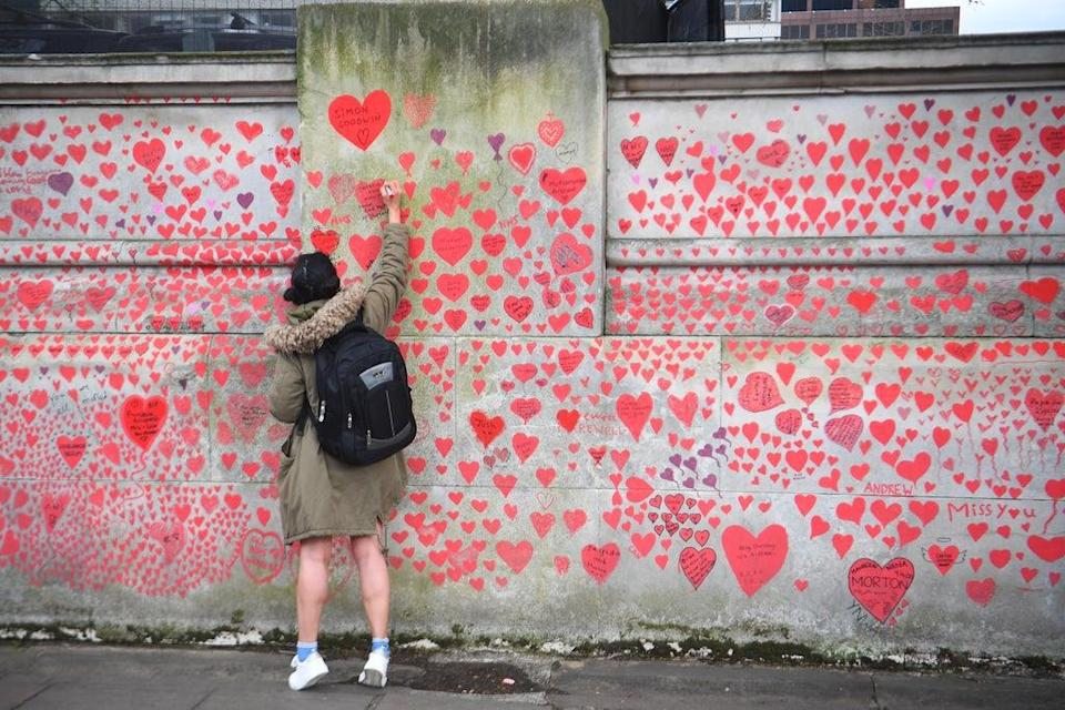 A woman writes in a heart on the Covid memorial wall on the Embankment in London (Victoria Jones/PA) (PA Wire)