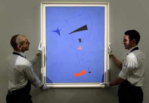 "Gallery assistants pose with artist Joan Miro's ""Peinture (Etolie Bleue), 1927"" at Sotheby's auction house"