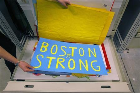 Archivist Crilly holds a poster, an artifact saved from the makeshift Boston Marathon bombing memorial, at the City Archives in Boston, Massachusetts