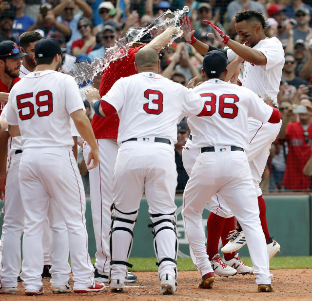Boston Red Sox' Xander Bogaerts, right, is greeted by teammates at home plate after hitting a grand slam in the 10th inning of a baseball game against the Toronto Blue Jays, Saturday, July 14, 2018, in Boston. The Red Sox won 6-2. (AP Photo/Winslow Townson)