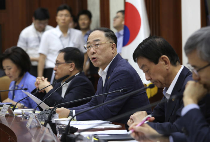 South Korean Economy and Finance Minister Hong Nam-ki, center, speaks as he presides over a meeting to discuss ways to respond to Japan's latest trade restrictions against South Korea at the government complex in Seoul, South Korea, Monday, Aug. 5, 2019. South Korea says it will spend 7.8 trillion won ($6.5 billion) over the next seven years to develop technologies for industrial materials and parts as it moves to reduce its dependence on Japan during an escalating trade row. (AP Photo/Ahn Young-joon)
