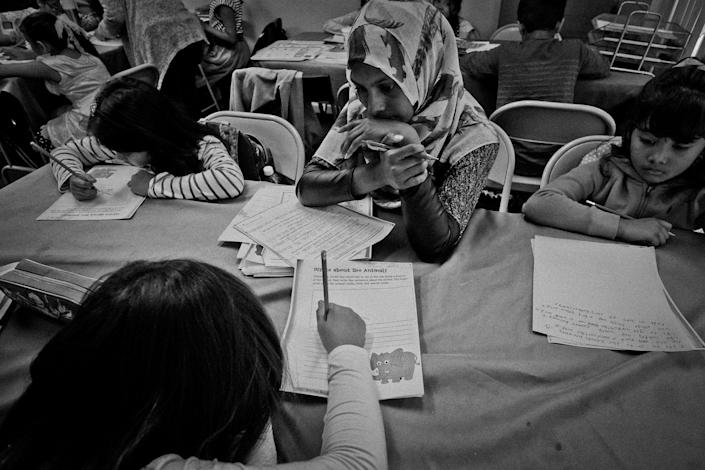 <p>Parents meet with teachers to get a student's progress at Kahn's Tutorial's Saturday class in Jackson Heights, Queens, N.Y., in October 2015. Tutorials help kids get into the best New York City high schools — kids of all ethnic backgrounds attend the school. (Photo: Yunghi Kim/Contact Press Images) </p>