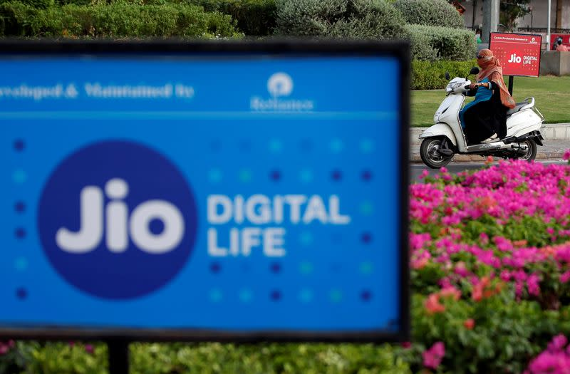 A woman rides her scooter past advertisements of Reliance Industries' Jio telecoms unit, in Ahmedabad