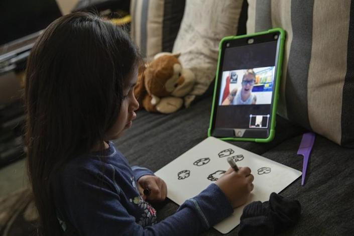 """A transitional kindergarten student draws clouds when asked remotely by her teacher to describe the weather in Orange on April 28. <span class=""""copyright"""">(Los Angeles Times)</span>"""