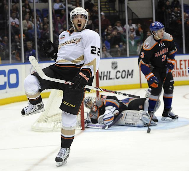 Anaheim Ducks' Mathieu Perreault (22) celebrates his goal against New York Islanders goalie Evgeni Nabokov (20) as Travis Hamonic (3) looks away during the period of an NHL hockey game Saturday, Dec. 21, 2013, in Uniondale, N.Y. The Ducks won 5-3. (AP Photo/Kathy Kmonicek)