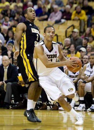 Missouri's Michael Dixon, right, drives past Kennesaw State's Delbert Love, left, as he heads toward the basket during the second half of an NCAA college basketball game, Thursday, Dec. 15, 2011, in Columbia, Mo. Missouri won the game 104-67. (AP Photo/L.G. Patterson)