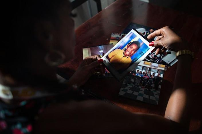 """Taloma Miller looks through a stack of photos of her late son Semaj and lingers on a school portrait of him when he was much younger. Semaj Miller, a 14-year-old basketball player with NBA potential according to some, was shot and killed in Compton on July 29. <span class=""""copyright"""">(Jason Armond / Los Angeles Times)</span>"""