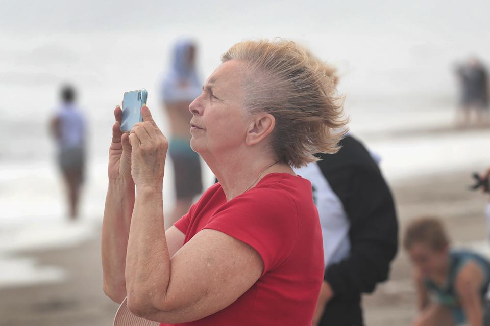 A woman takes a photo as visitors gather on the beach during high tide as Hurricane Dorian approaches in Indialantic, Florida.
