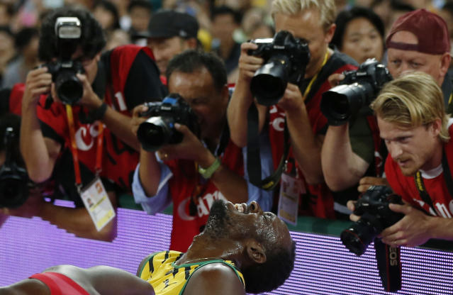 Photographers take pictures of Usain Bolt of Jamaica after he won the men's 200 metres final during the 15th IAAF World Championships at the National Stadium in Beijing