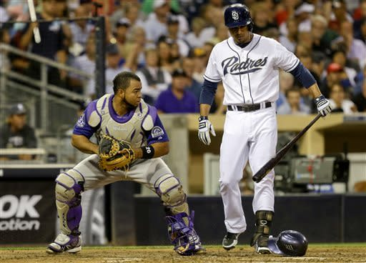 Colorado Rockies catcher Wilin Rosario, left, looks toward the San Diego Padres' runner on third base after retrieving a pitch that bounced away as Padres' batter Jesus Guzman, right, steps out of the way in the third inning of a baseball game in San Diego, Tuesday, July 9, 2013. (AP Photo/Lenny Ignelzi)