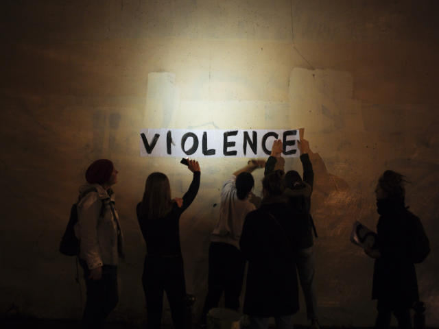 "The word ""violence"" is pasted onto a wall by a group of women in a dark street in Paris. In Paris and cities across France, the signs are everywhere. ""Complaints ignored, women killed"" and ""She leaves him, he kills her,"" they read in black block letters pasted over stately municipal buildings. Under cover of night, activists have glued them to the walls to draw attention to domestic violence, a problem French President Emmanuel Macron has called ""France's shame."" (Photo: Kamil Zihnioglu/AP)"
