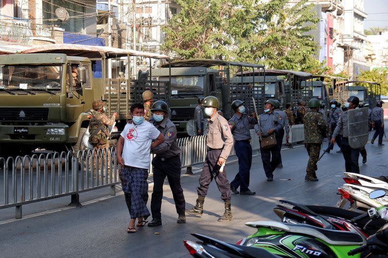 Police detains a man during a protest against the military coup in Mandalay