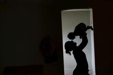 Rosana Vieira Alves holds her four-month-old daughter Luana Vieira, who was born with microcephaly, at their house in Olinda, Brazil, February 3, 2016. REUTERS/Ueslei Marcelino/Files