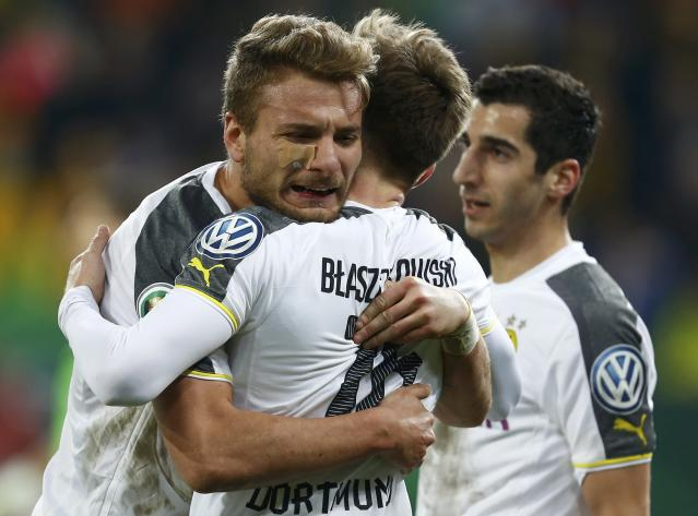 Borussia Dortmund's Italian striker Ciro Immobile (L) celebrates his second goal against Dynamo Dresden with fellow team mates Polish striker Jakub Blaszczykowski and Henrikh Mkhitaryan (R) during their German Cup (DFB Pokal) soccer match against in Dresden March 3, 2015. REUTERS/Hannibal Hanschke (GERMANY - Tags: SOCCER SPORT TPX IMAGES OF THE DAY) DFB RULES PROHIBIT USE IN MMS SERVICES VIA HANDHELD DEVICES UNTIL TWO HOURS AFTER A MATCH AND ANY USAGE ON INTERNET OR ONLINE MEDIA SIMULATING VIDEO FOOTAGE DURING THE MATCH.